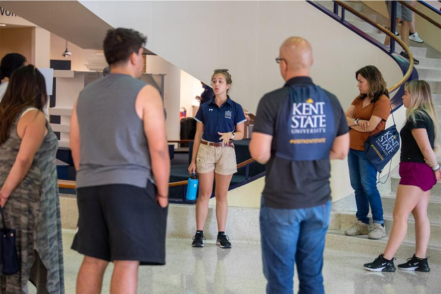 Students stand in a circle around a campus guide during a tour on the Kent Campus in the Kent Student Center.