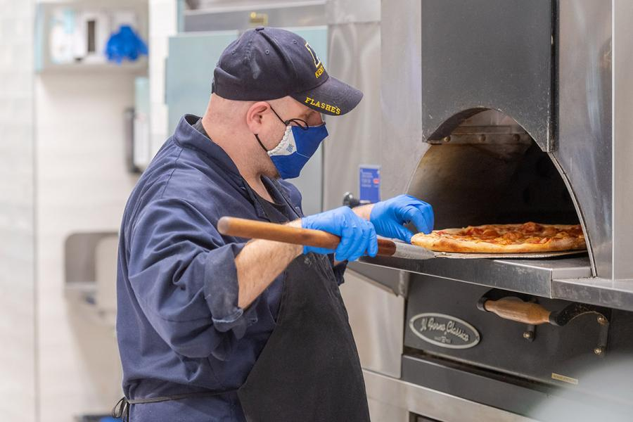 A Kent State employee loads a pizza into the oven.