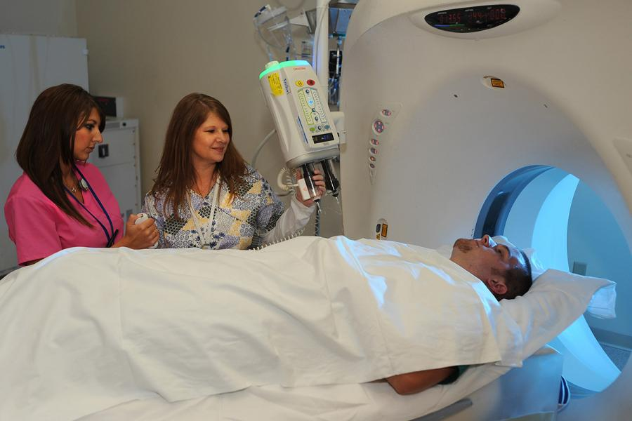 A radiologist at Robinson Memorial Hospital shows a Kent State student how to prepare a patient for a CT scan.