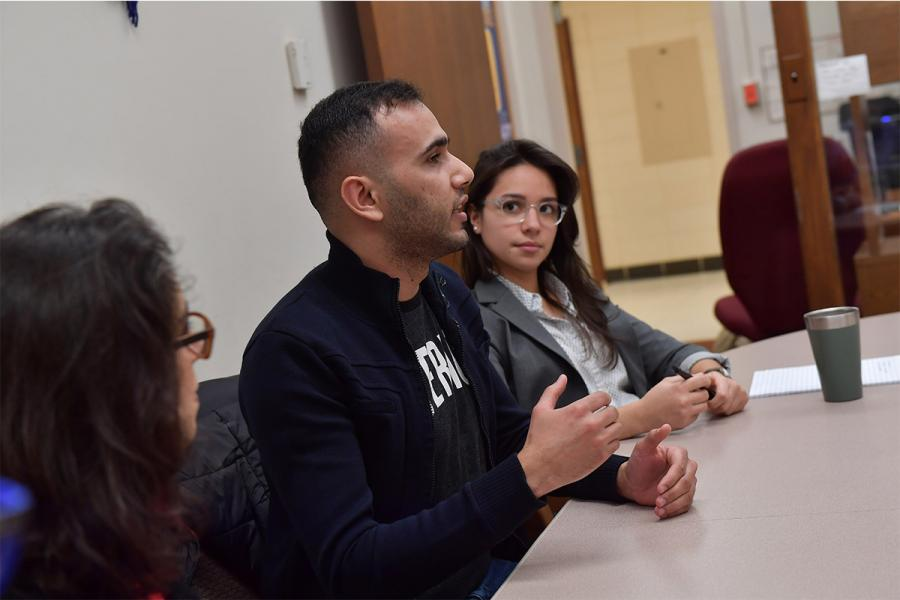 An international student sits at a conference room table with his hands expressively moving as he talks during a discussion.