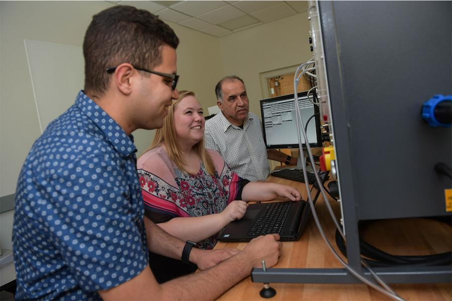 Two Kent State research students work together with a professor looking on at a computer during the summer.