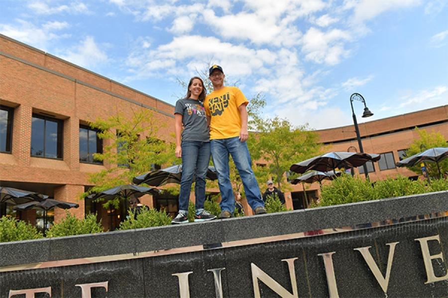 Two students stand, smiling on the fountain in Risman Plaza, near the Kent Student Center.