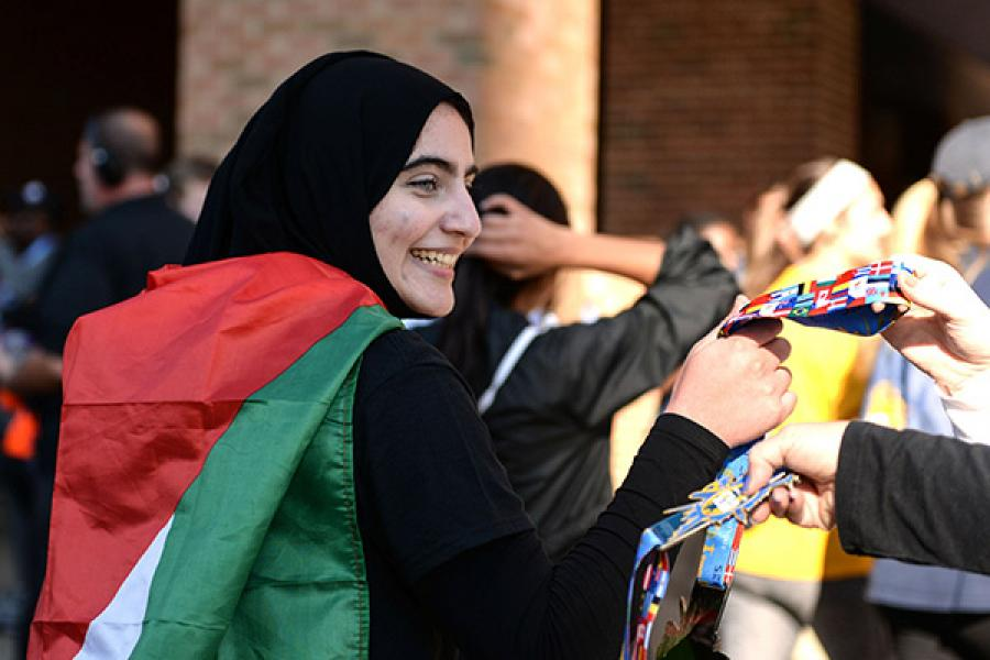 A student looks to the side, smiling during an on campus event with native country flags.