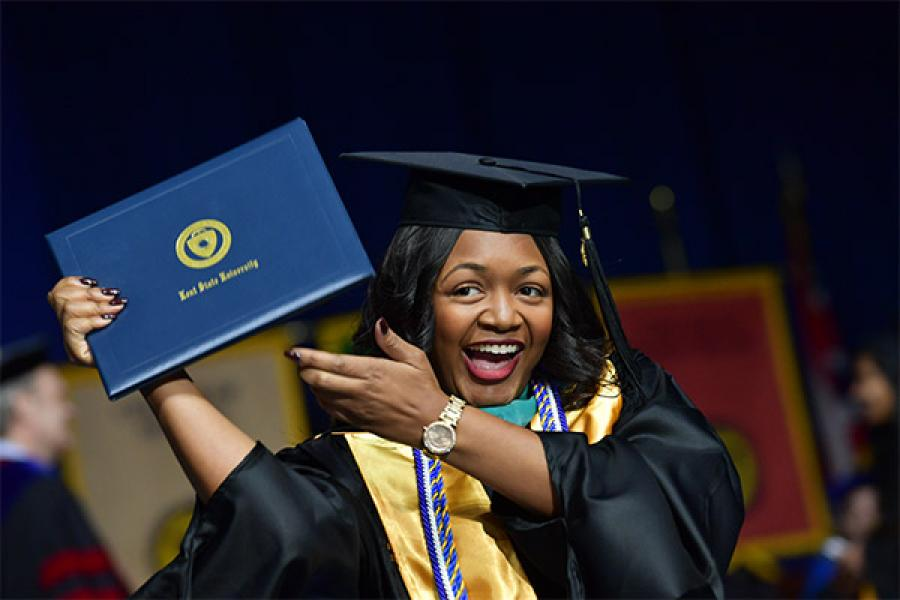 A recent Kent State graduate smiles holding a diploma.