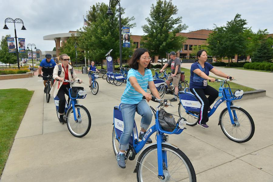 A diverse group of students rides bicycles on the Kent Campus