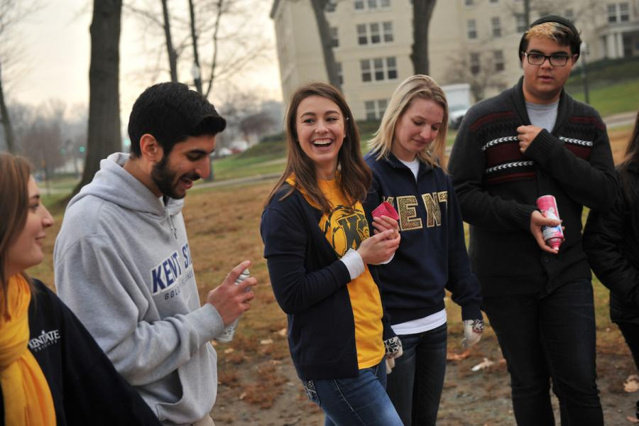 Students walk and talk outside of a residence hall