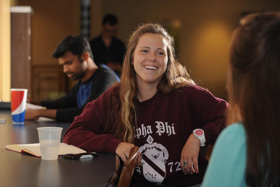 Student sits at a table and chats with another student