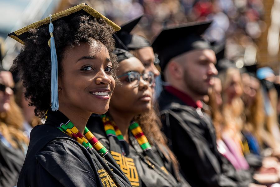 A Kent State graduate smiles at the camera during an outdoor commencement ceremony.