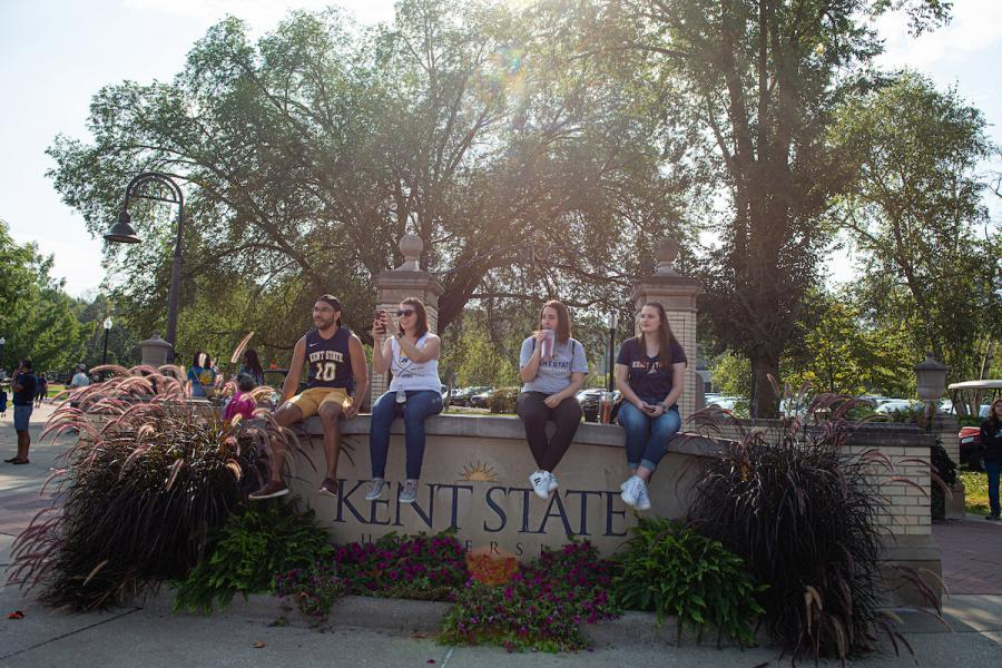 Students sit on front campus Kent State sign and watch, smiling as cars drive past on Main Street in Kent.