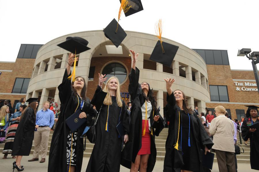 Kent State graduates throw graduation caps in the air
