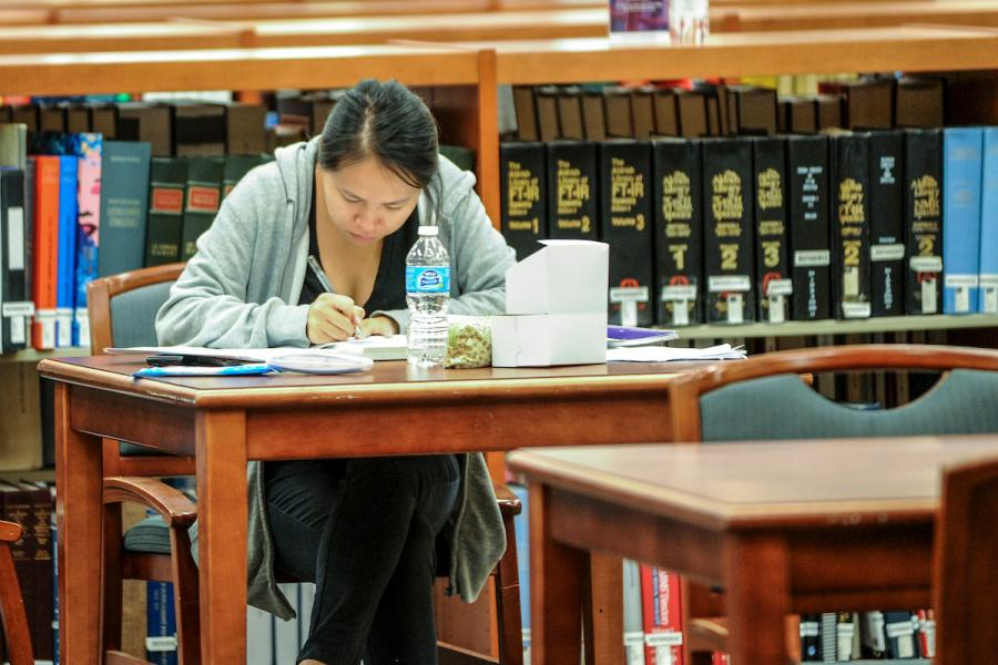 Student takes notes in the library