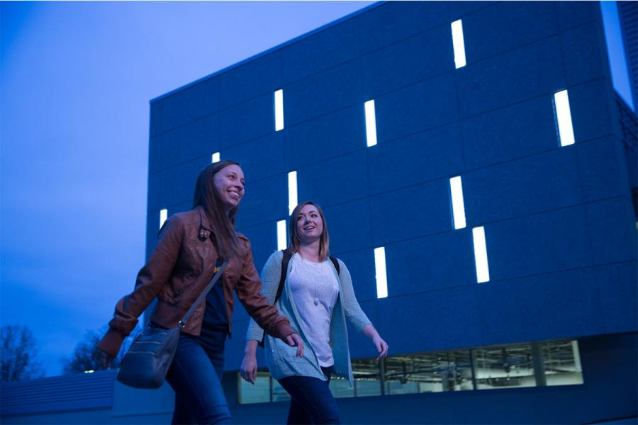 Two students walk during dusk on the Kent Campus.