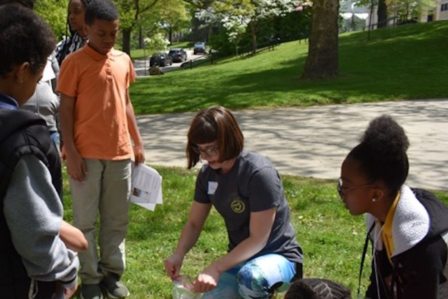 Kent State Department of Geology graduate student Kortney Cole shows Schumacher Elementary School sixth grader students how to collect soil samples.