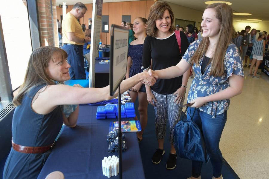 A future Kent State student shakes the hand of a Kent State employee while visiting the Kent Student Center.