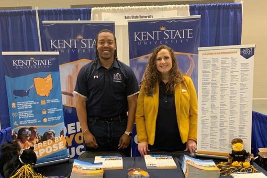 Admissions counselors pose for a photo at a college fair