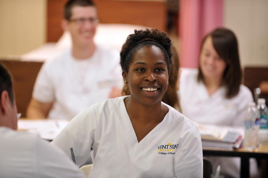 A smiling nursing student looks on during a nursing class.