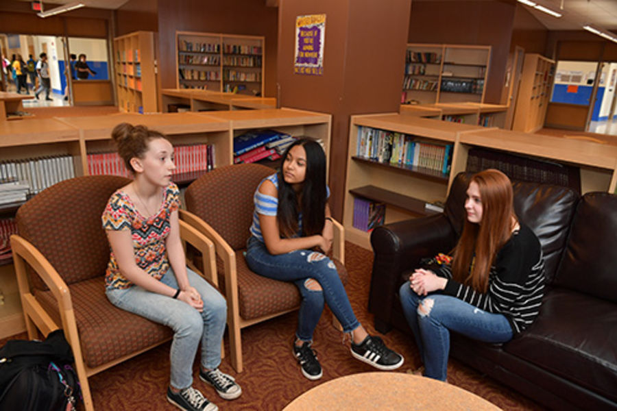 A group of students talking in the library.