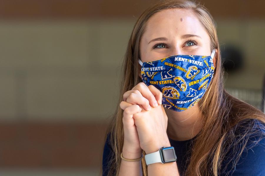 A student smiles and looks up from her computer, while wearing a Kent State mask during the COVID-19 pandemic.