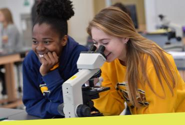 Photo of two students in lab, looking into a microscope