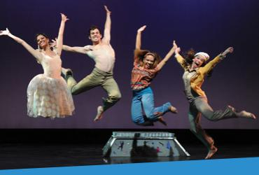 Photo of students, performing in a play, jumping in the air