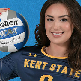 Girl in Kent State volleyball uniform smiles and cradles volleyball on shoulder.