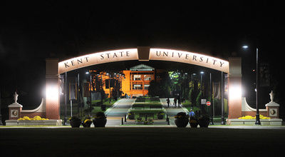 The Lester A. Lefton esplanade Arch is lit up at night, welcoming visitors and students to campus from downtown Kent.