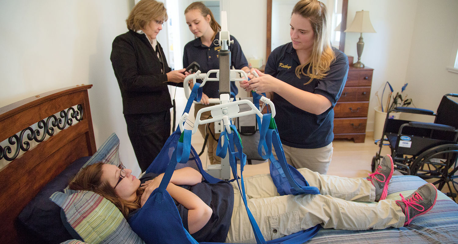 East Liverpool: In one bedroom, students use a Hoyer lift to practice transferring a patient from a wheelchair to a bed. Another bedroom simulates a hospital room so students can learn to work around cords and tubing.