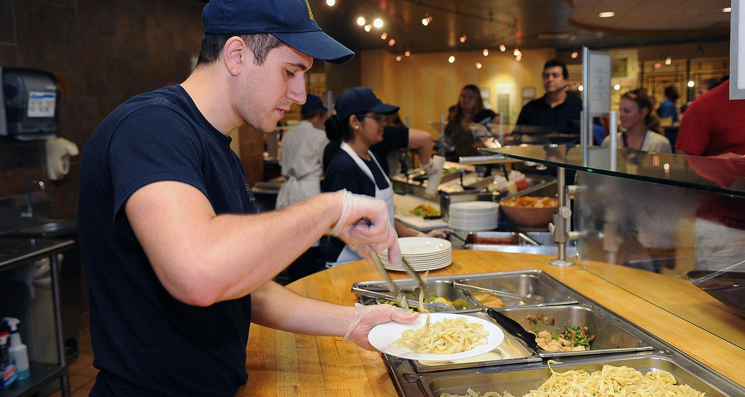 A Kent State student worker prepares a plate of food at Eastway Center.