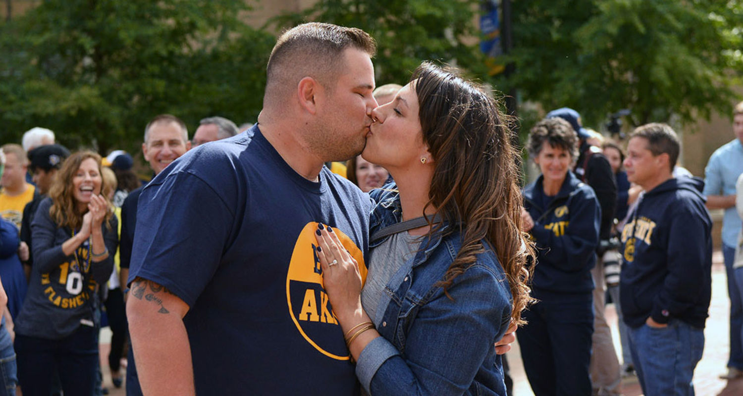 Kent State student Adam Fletcher and alumna Krystin Smith,'13, embrace during the annual Kiss on the K event, held on Risman Plaza during Homecoming 2016. Fletcher and Smith got engaged during the Kiss on the K event.