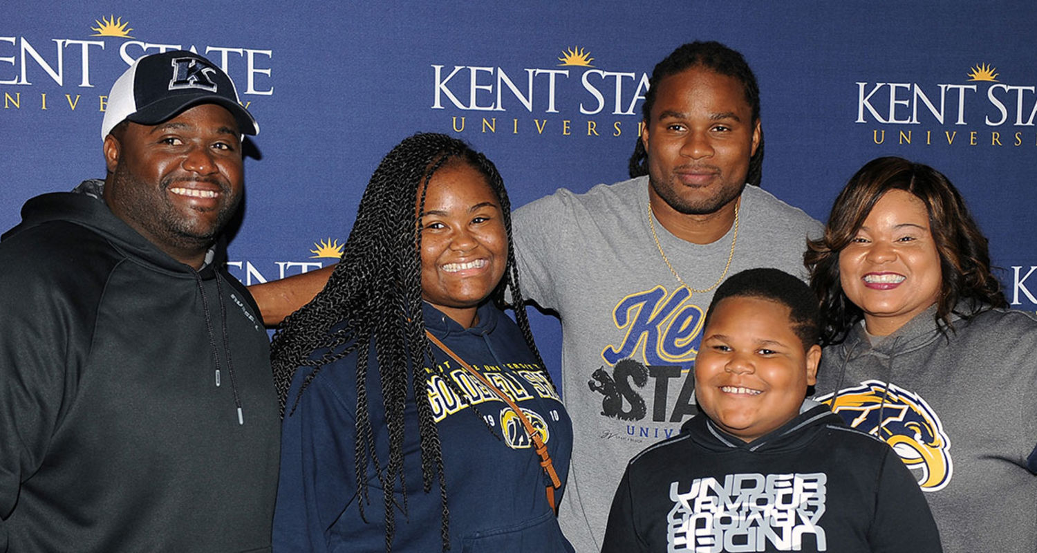 Kent State students and family members pose for a photo with alumnus Josh Cribbs, '10, in the Center for Philanthropy and Alumni Engagement during 2016 Homecoming events.
