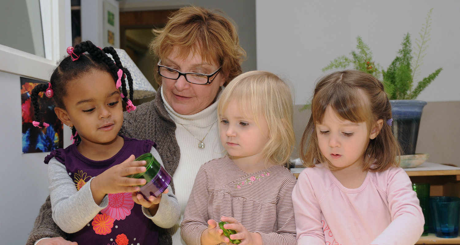 A staff member engages children at the Child Development Center