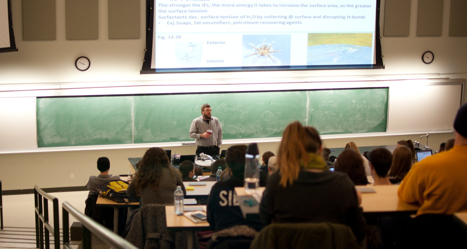 A professor teaches general chemistry in the large lecture hall.