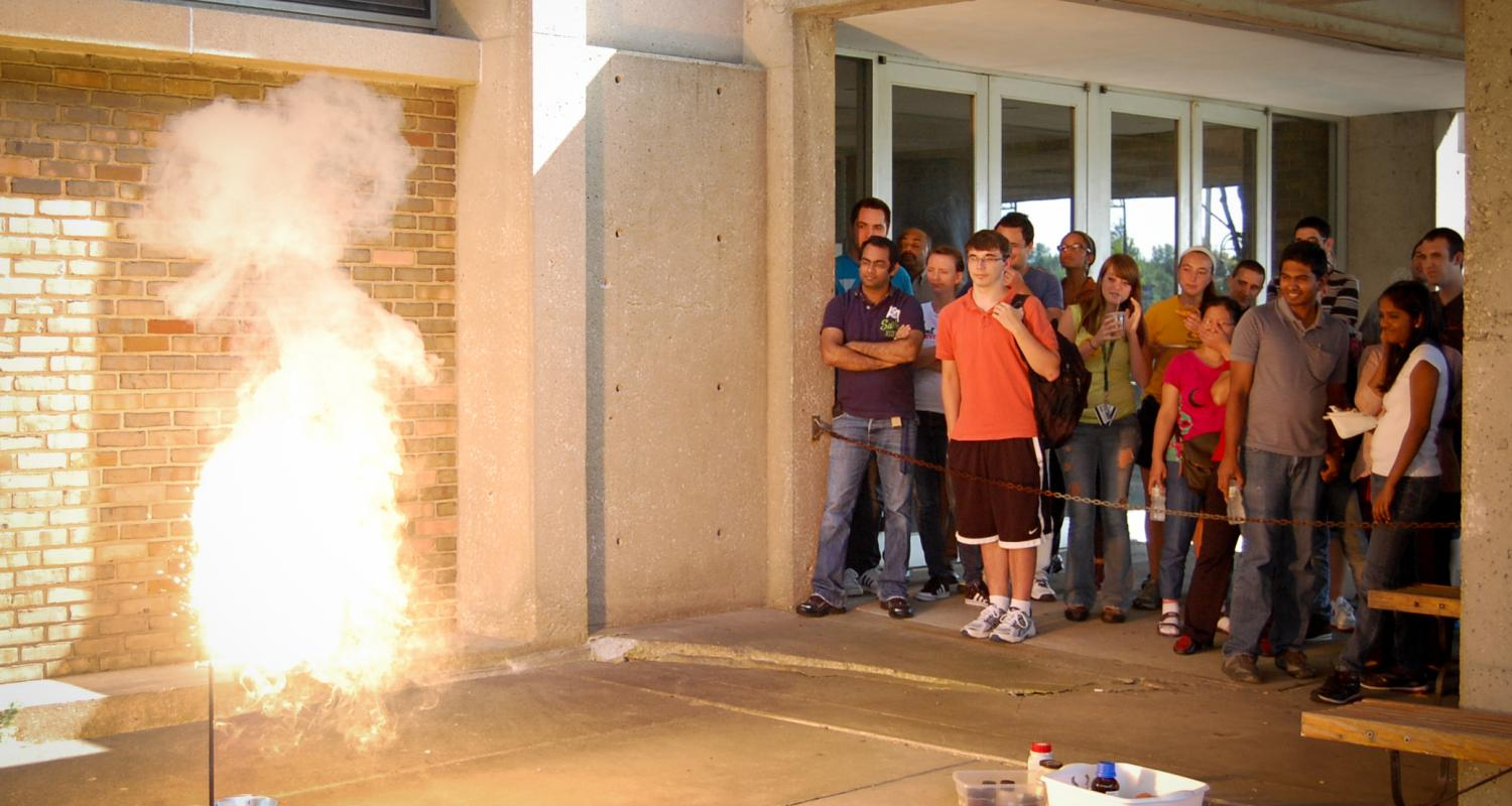 Students watch a thermite reaction take place in front of Williams Hall.