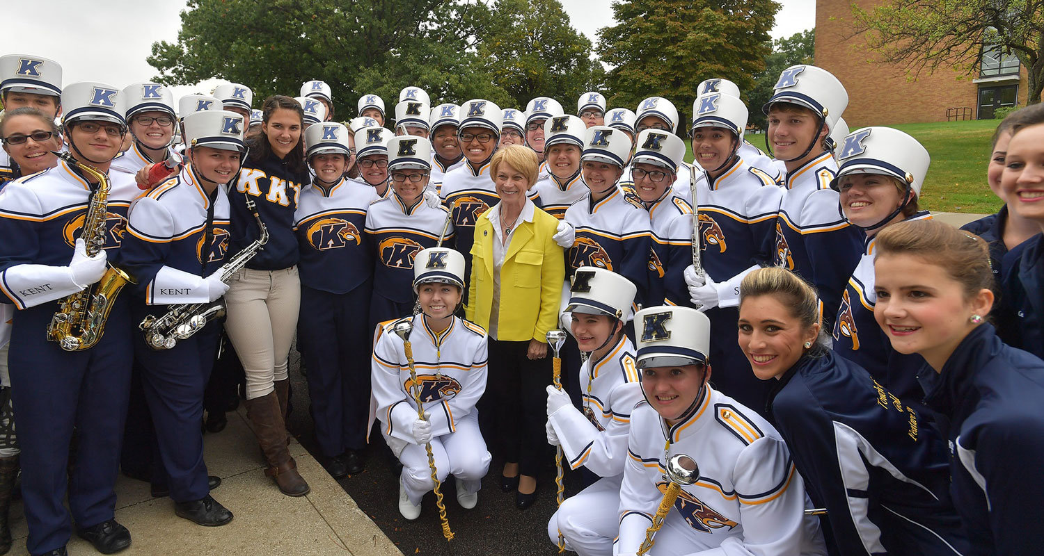 Kent State President Beverly Warren smiles with members of the Kent State Marching Golden Flashes before the 2016 Homecoming Parade.