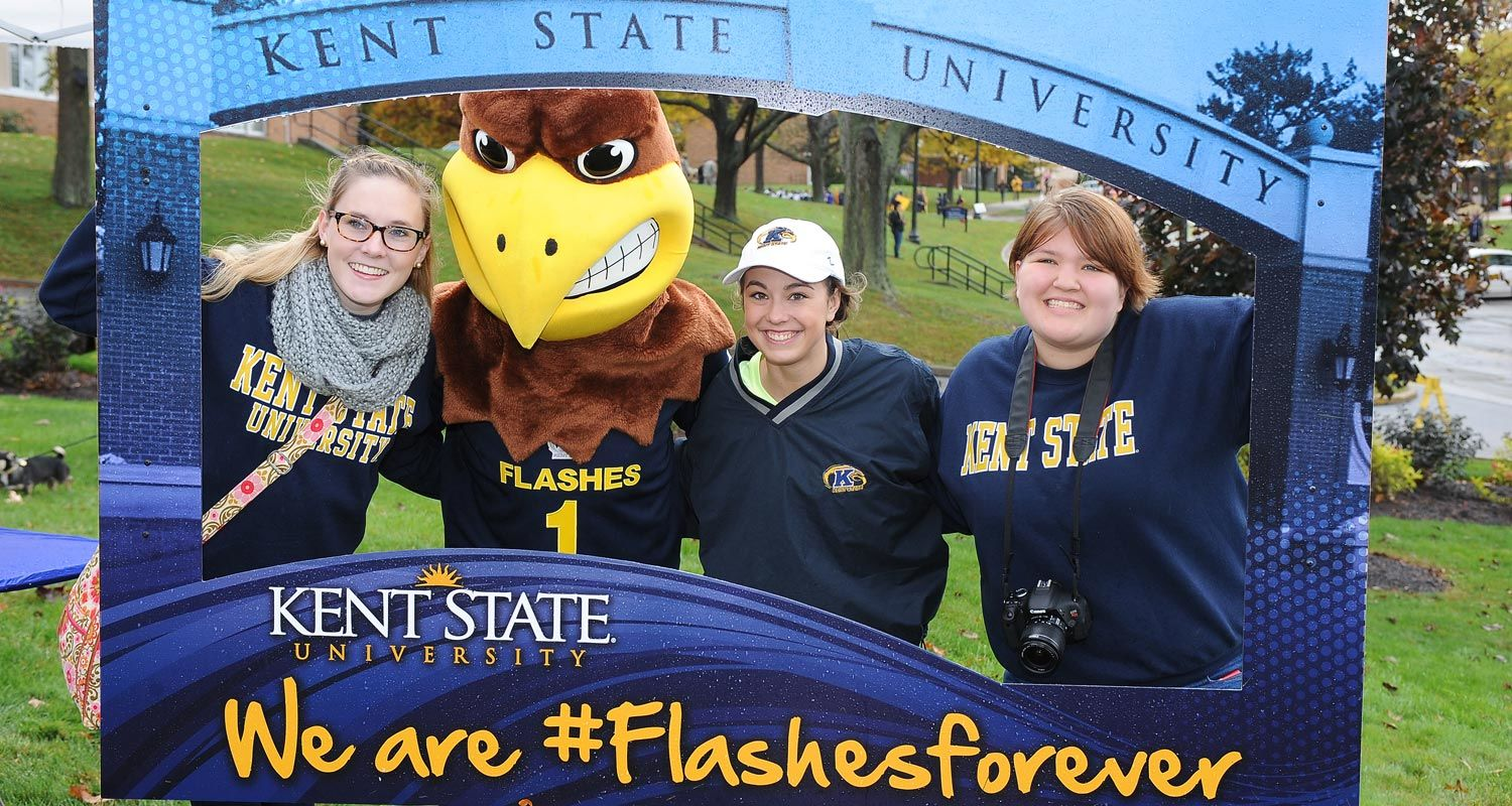 Kent State students pose with Flash, the university's mascot, in a #FlashesForever photo frame during Homecoming.