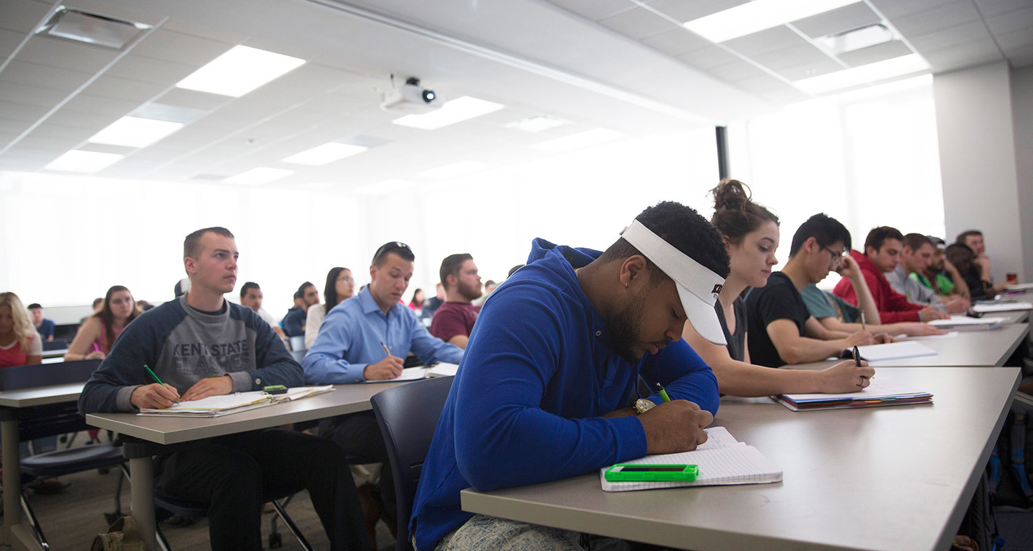 Kent State University students take notes during a classroom lecture. Fourteen faculty members have been presented with the President's Faculty Excellence Award, which recognizes exceptional performance.