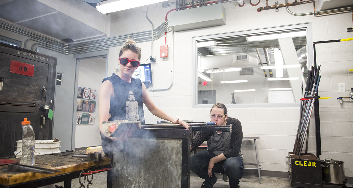 Students collaborate in the glass blowing studio.