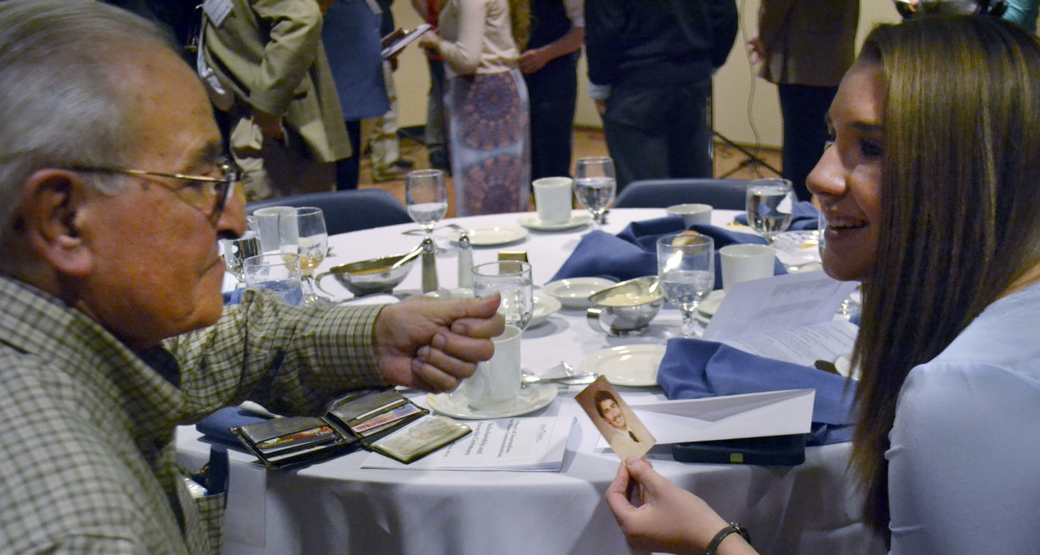 A donor speaks with a scholarship recipient during a scholarship dinner