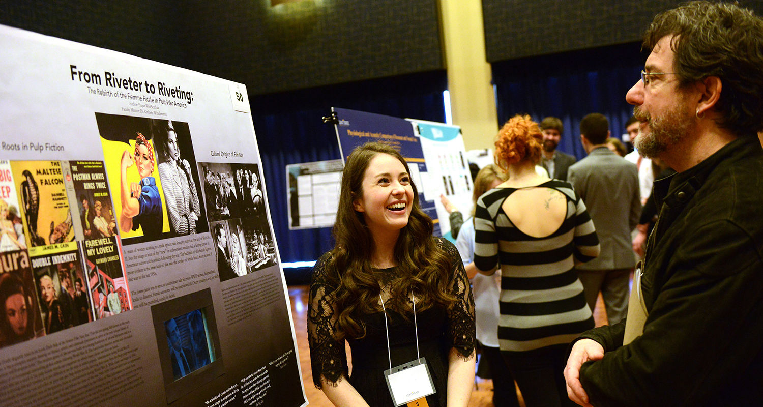A Kent State student shows her research work off to Kenneth Bindas, Ph.D., chair of the university's Department of History, during the Undergraduate Research Symposium. The student studied the role of females in post-World War II America.