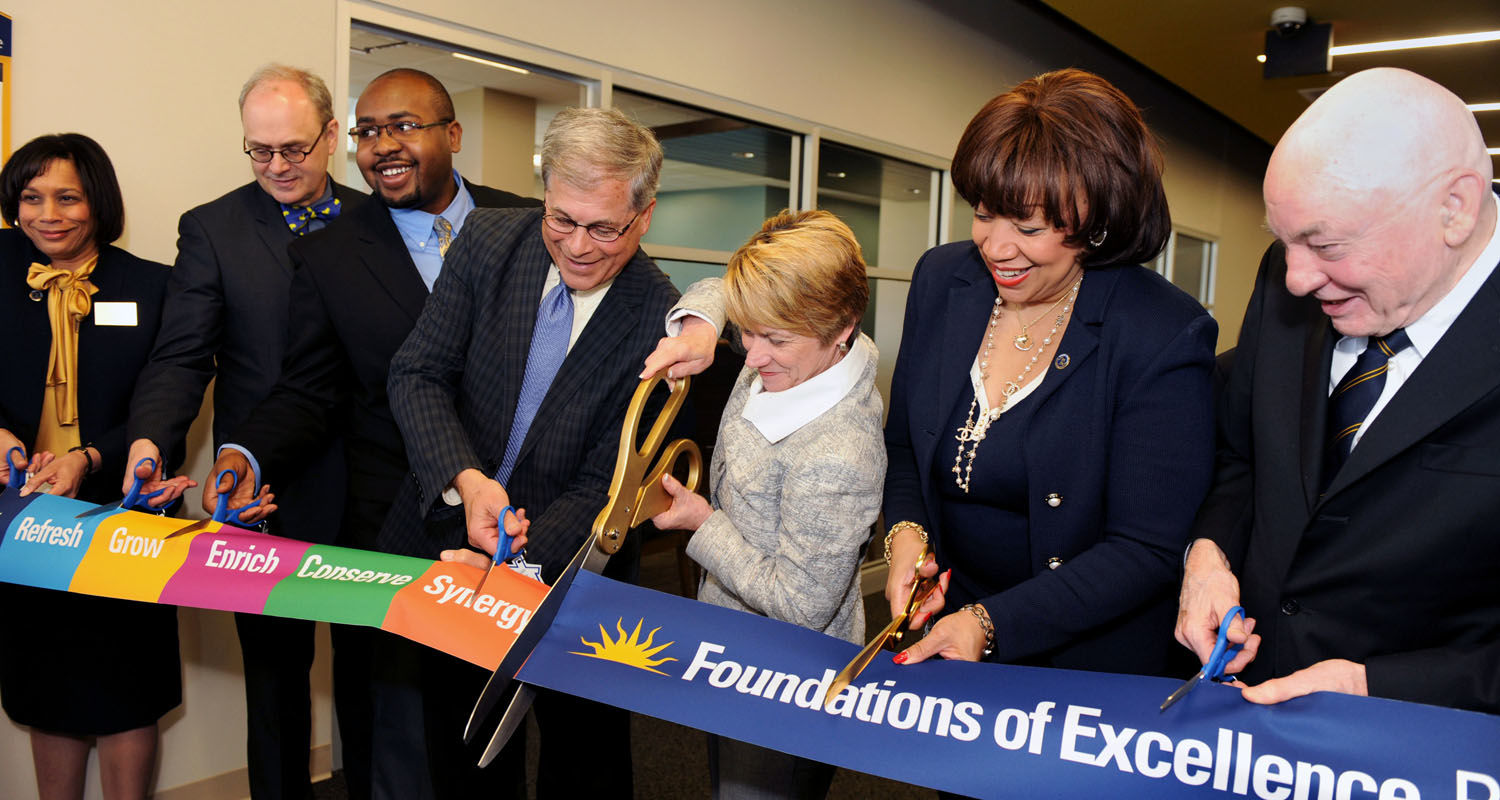 Kent State President Beverly Warren (center) leads the way while Board of Trustees Chair Dennis Eckart (to her left) and other Kent State dignitaries cut the ribbon for the official grand opening of the new Center for Undergraduate Excellence, or the CUE.