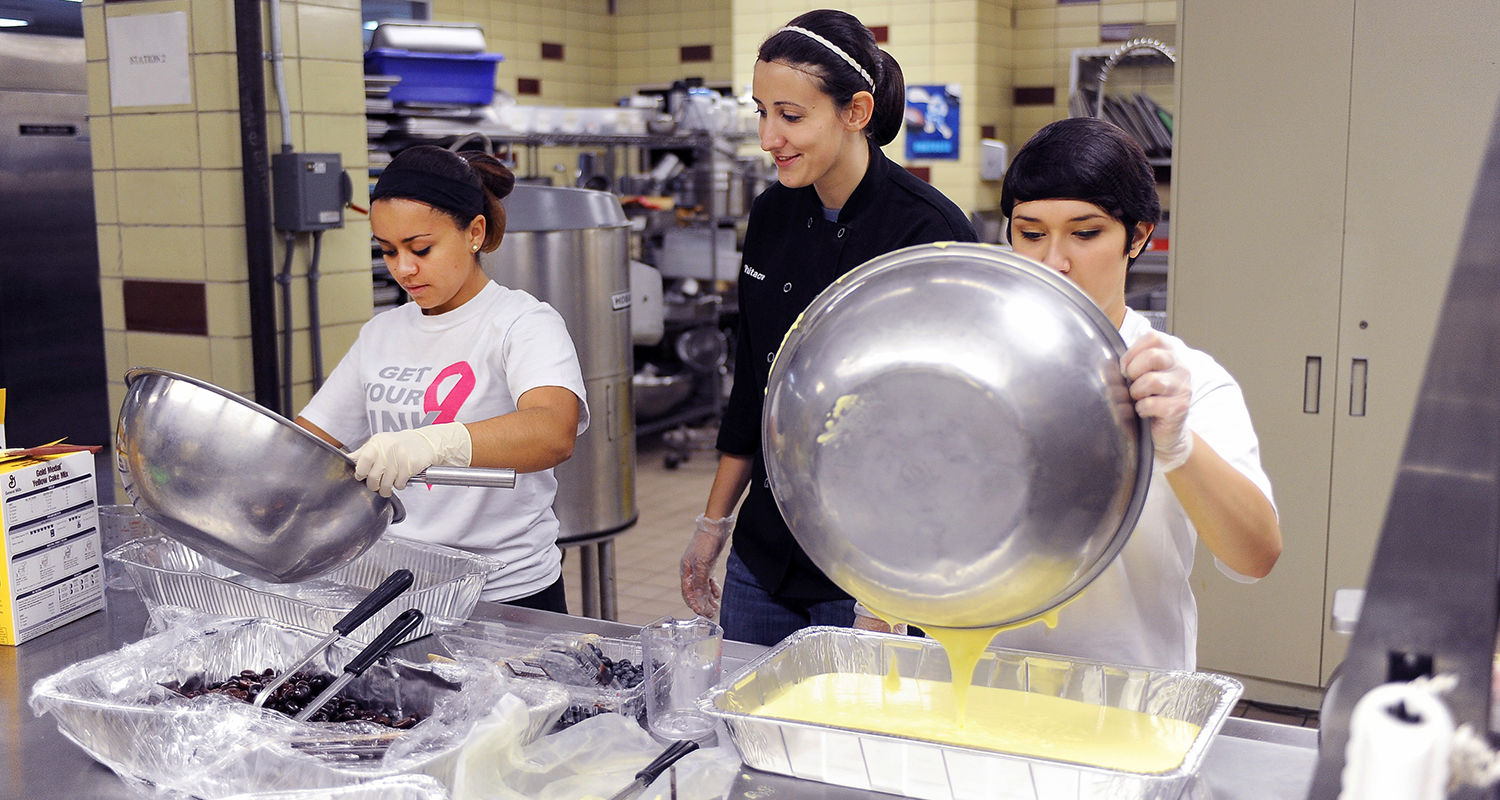 Students team up to prepare meals in the Campus Kitchen at Kent State, located in the second floor kitchen in Beall Hall.