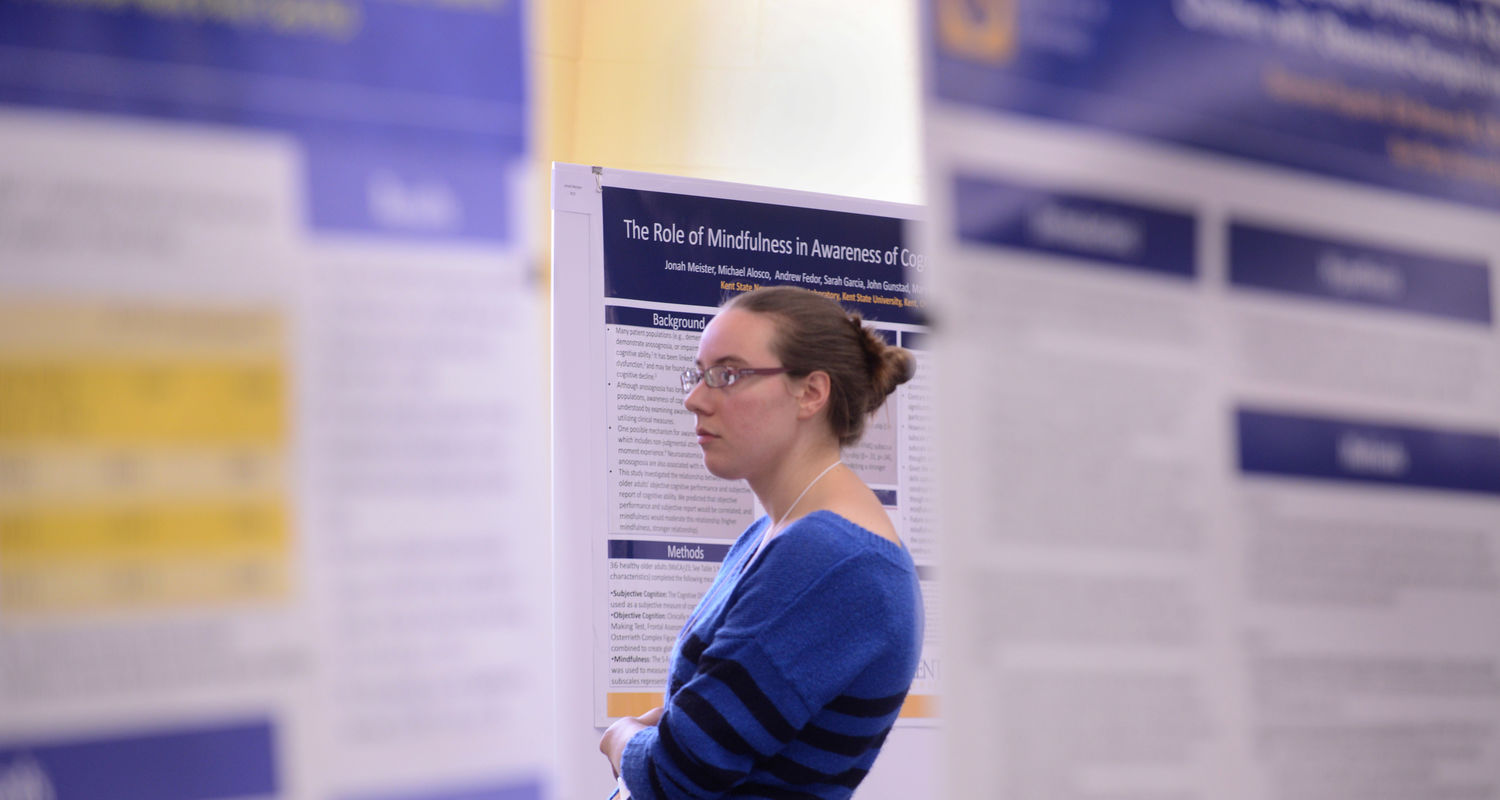 A student looks at posters during a rcent undergraduate research symposium held on the fourth floor of the library.