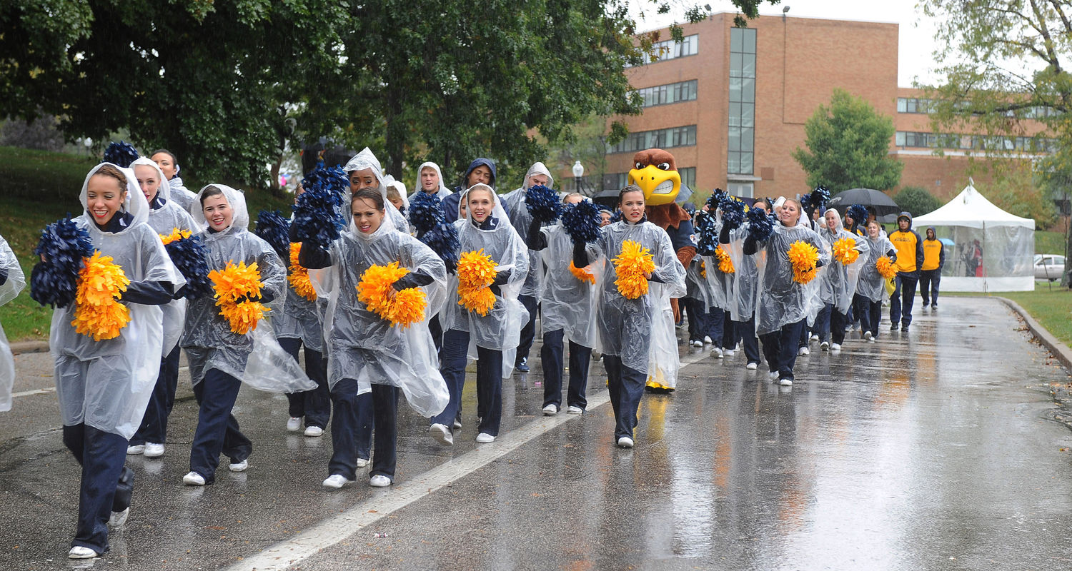The Kent State cheerleaders make their way along a rainy parade route during the 2015 Homecoming celebration near Williamson Alumni Center.
