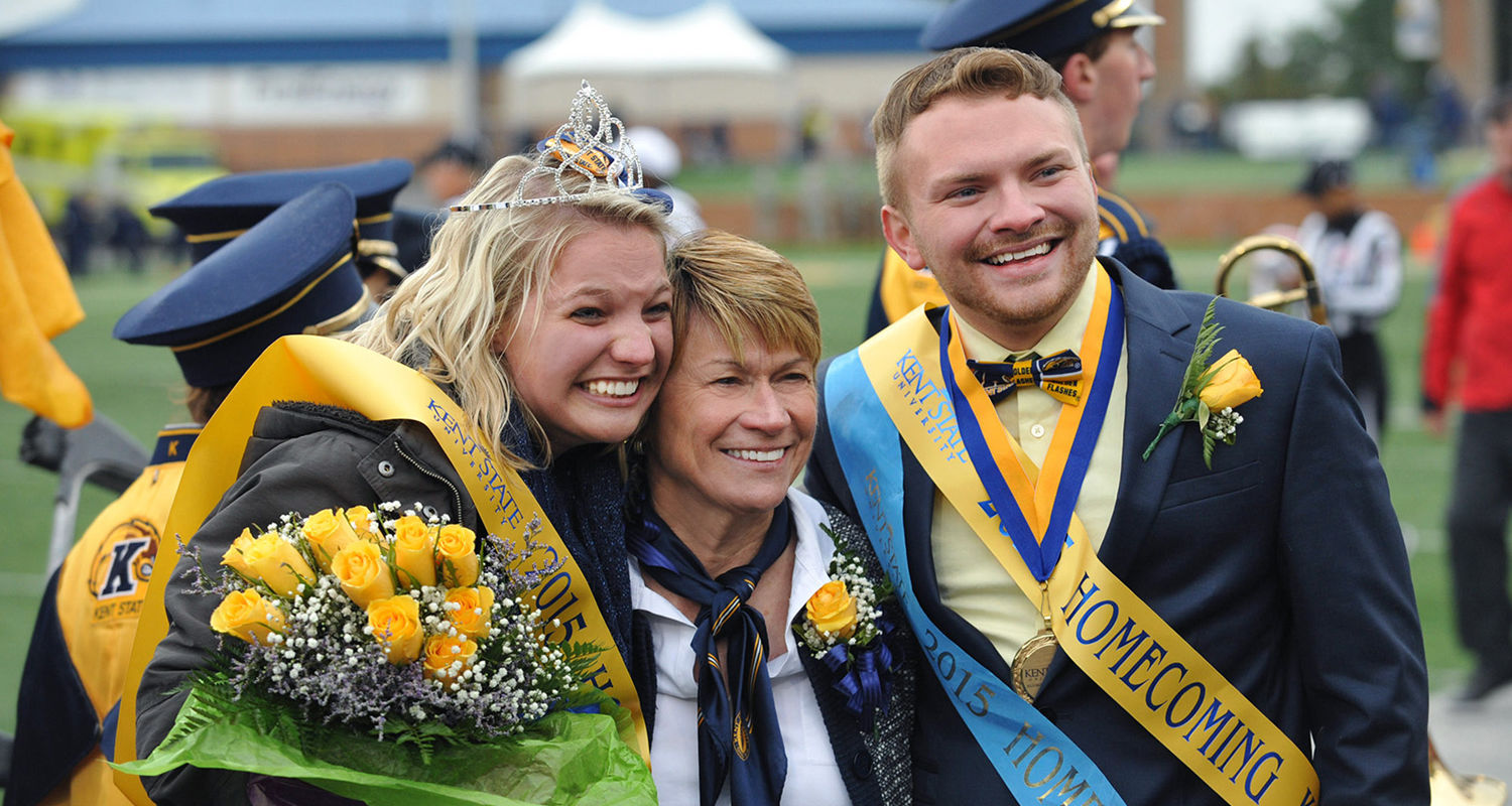 Amanda Bevington (left) and Terry Hugo III celebrate with Kent State President Beverly Warren after being named Homecoming King and Queen during the 2015 festivities at Dix Stadium.