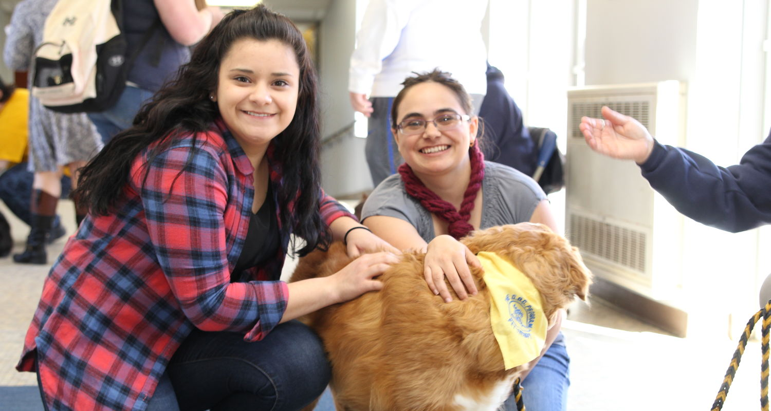 Two female Kent State Ashtabula students pet one of the Dogs on Campus pet therapy dogs druing a visit to campus