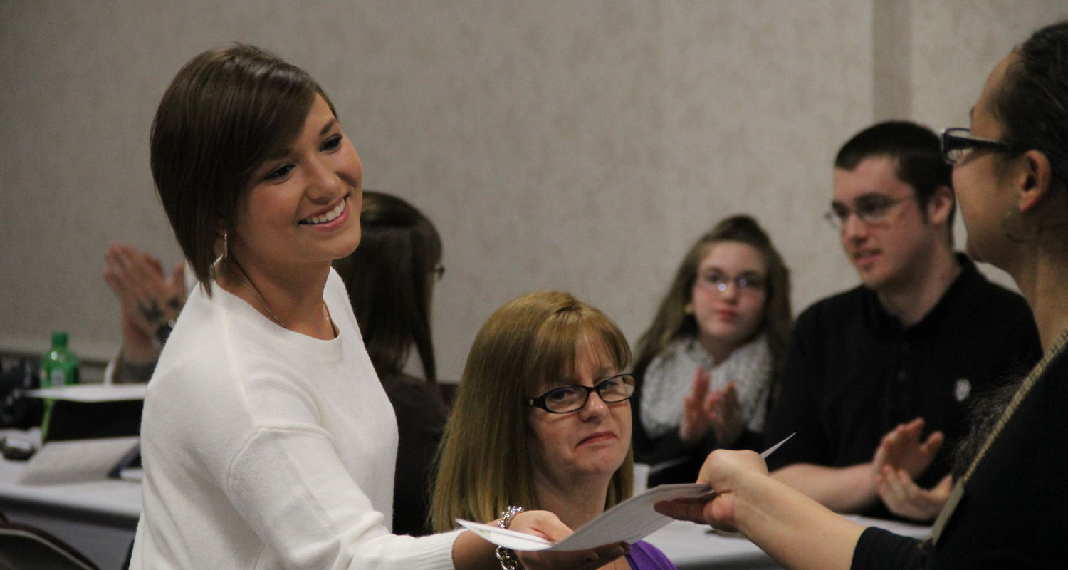 A student receives her certificate during the President & Dean's List Reception
