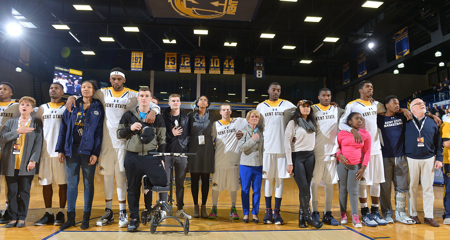 Kent State men's basketball players stand in unity with fans of a different race selected from the crowd during the national anthem.
