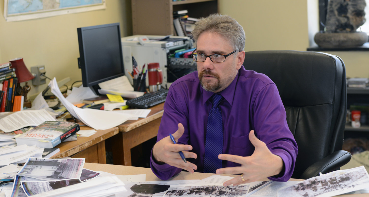 James Tyner, Ph.D., professor in Kent State's Department of Geography, discusses his research in his office.