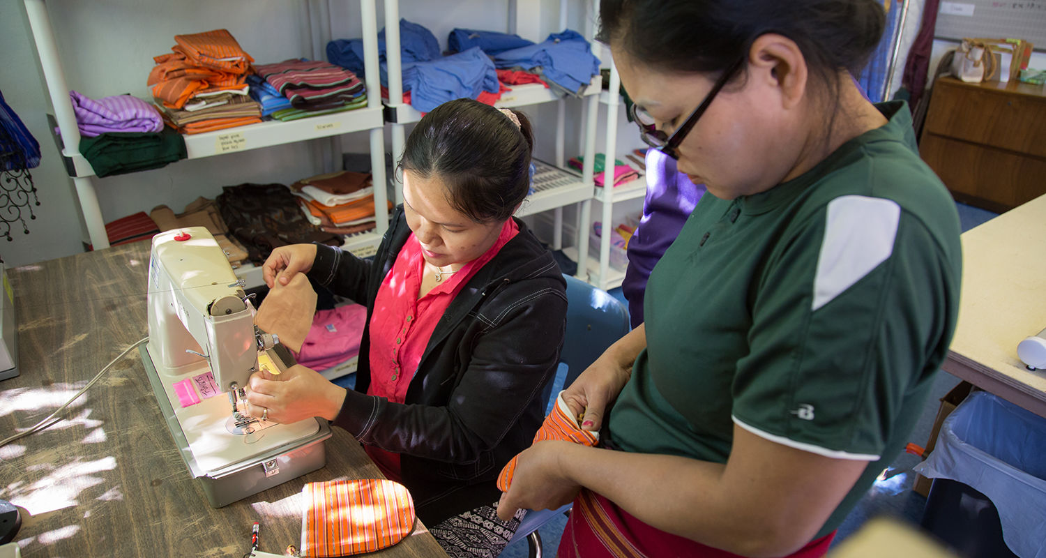 Ka Naw examines the quality of a half moon pouch as she trains seamstress Kaser Paw at Neighbors Apparel.