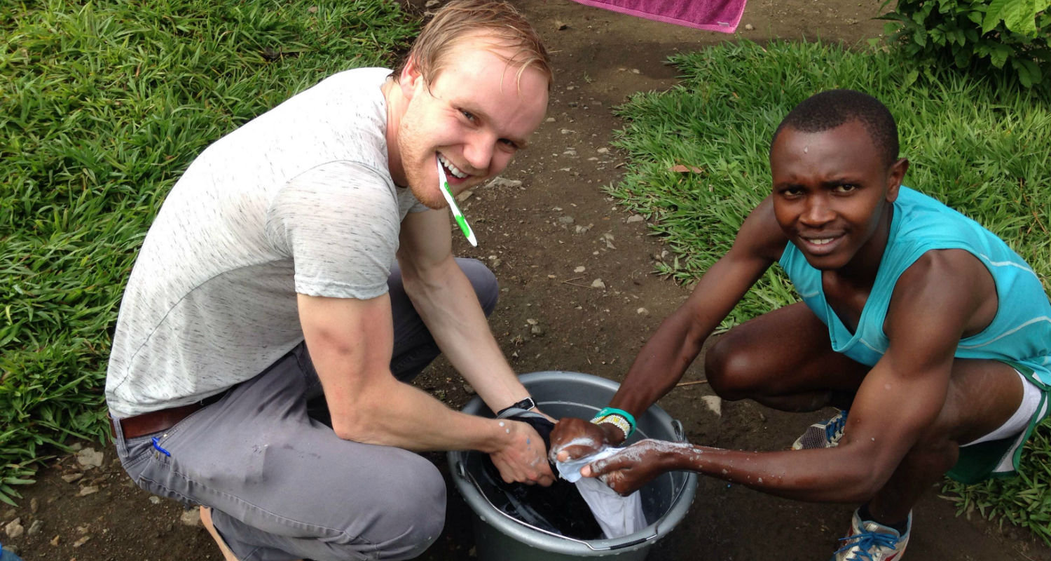 Graduate student Daniel Socha works with a member of the Project Kirotshe running team on how to wash his running clothes.